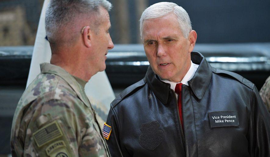 U.S. Vice President Mike Pence speaks to Gen. Nick Nicholson, commander of U.S. forces in Afghanistan, in a hangar at Bagram Air Base in Afghanistan on Thursday, Dec. 21, 2017. (Mandel Ngan/Pool via AP)