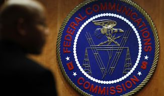 This Thursday, Dec. 14, 2017, photo, shows the seal of the Federal Communications Commission before a meeting in Washington. On Thursday, Dec. 21, 2017, the FCC proposed a $13.4 million fine on TV-station owner Sinclair for not identifying paid programming as advertising. (AP Photo/Jacquelyn Martin)