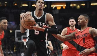San Antonio Spurs guard Dejounte Murray drives to the basket past Portland Trail Blazers guard Damian Lillard during the first half of an NBA basketball game in Portland, Ore., Wednesday, Dec. 20, 2017. (AP Photo/Steve Dykes)