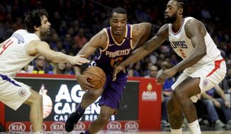 Phoenix Suns forward TJ Warren, middle, drives to the basket between Los Angeles Clippers guard Milos Teodosic, left, and center DeAndre Jordan during the first half of an NBA basketball game in Los Angeles, Wednesday, Dec. 20, 2017. (AP Photo/Chris Carlson)
