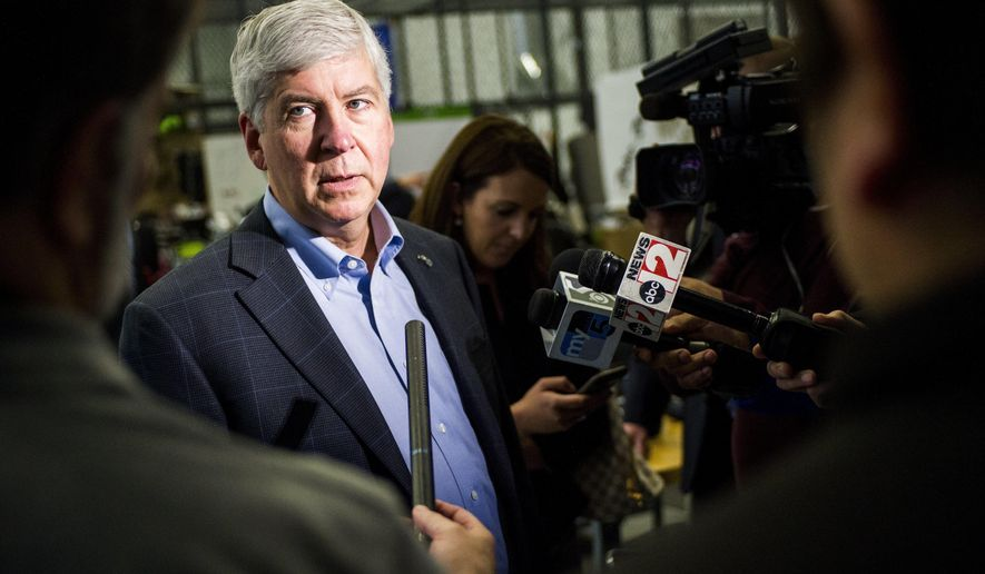 FILE - In this Nov. 6, 2017 file photo, Gov. Rick Snyder answers media questions in Flint, Mich. Snyder said Thursday, Dec. 21 the federal tax overhaul will cause residents' state income taxes to increase, and he's committed to ensuring taxpayers ultimately don't have to pay more. The tax legislation, which President Donald Trump will sign, will eliminate the $4,050 personal exemption. That's an issue because Michigan lets people claim a $4,000 exemption for each exemption taken on their federal return.  (Jake May /The Flint Journal-MLive.com via AP, File)