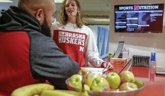In this Jan. 19, 2017, photo, Lindsey Remmers, University of Nebraska's director of performance nutrition, speaks to Mark Philipp, head football strength coach, in Lincoln, Neb. Nebraska will spend $3.3 million this year on athlete nutrition. In addition to the high-quality food at the training table and healthy snacks at fueling stations, the budget covers a director of food service, executive chef, registered sports dietitian and three assistants and more than a dozen other staffers. (AP Photo/Nati Harnik)