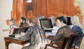 In this court room drawing, defendant Mehmet Atilla, center, reviews documents during the second day of jury deliberations in his corruption trial, Thursday, Dec. 21, 2017 in New York. The Turkish banker is accused of helping Iran evade U.S. sanctions and launder billions of dollars in oil revenue. At left is defense attorney Victor Rocco and defense attorney Cathy Fleming is at right. (Elizabeth Williams via AP)