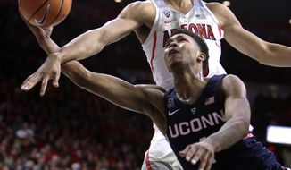 Arizona forward Keanu Pinder, top, fouls Connecticut guard Jalen Adams (4) during the first half of an NCAA college basketball game Thursday, Dec. 21, 2017, in Tucson, Ariz. (AP Photo/Rick Scuteri)