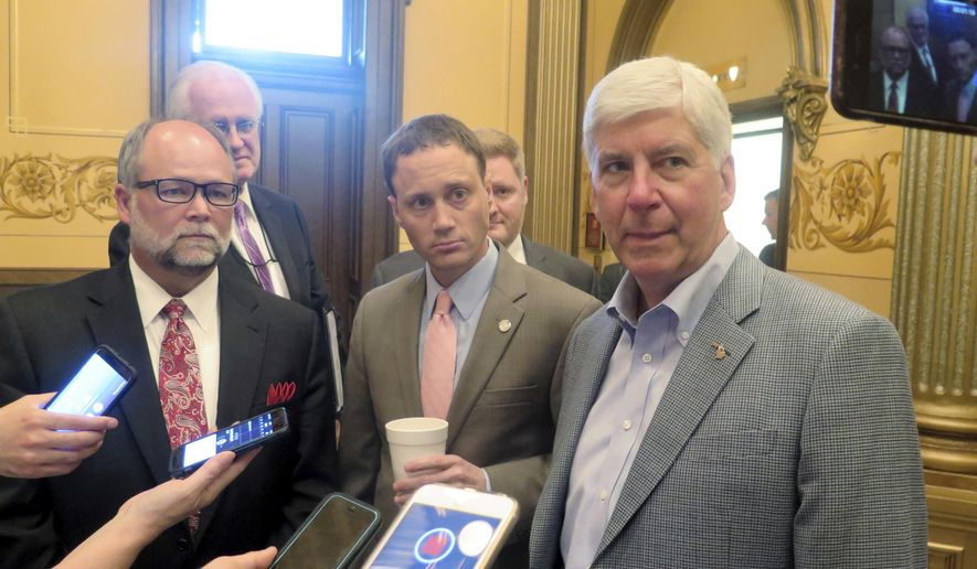 FILE - in this June 13, 2017 file photo, Michigan Gov. Rick Snyder, right, House Speaker Tom Leonard, center, and Senate Majority Leader Arlan Meekhof, left, speak to reporters at the Capitol in Lansing, Mich. New economic development tax incentives and the cost of retirement benefits for public-sector workers dominated Michigan's legislative agenda in 2017. The Republican governor signed 245 bills as of Thursday, Dec. 21, with many more awaiting his signature after a burst of voting in recent weeks. (AP Photo/David Eggert File)