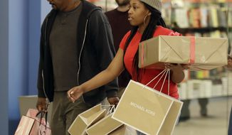 A couple carries their packages after holiday shopping at Concord Mills mall in Concord, N.C., Thursday, Dec. 21, 2017. (AP Photo/Chuck Burton)