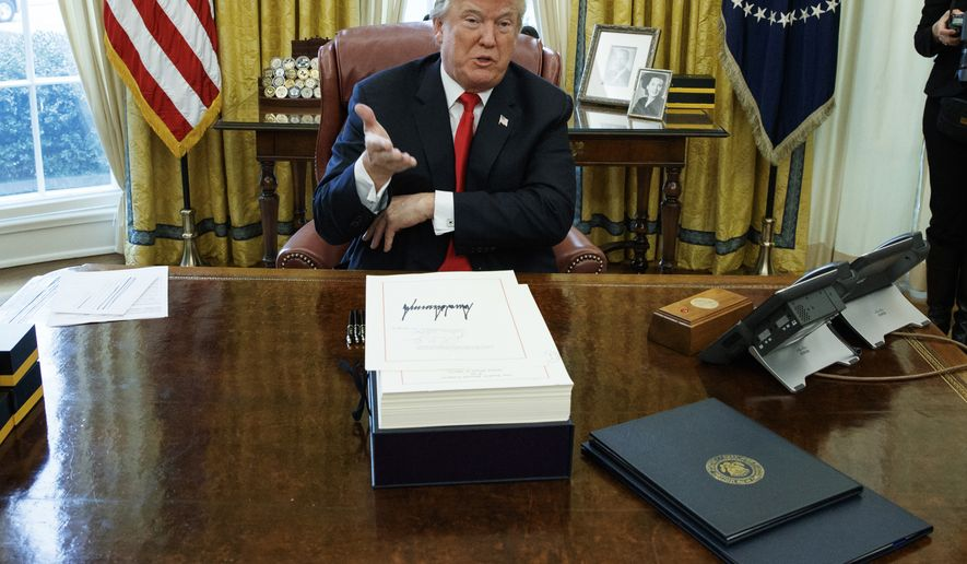 President Donald Trump speaks with reporters after signing the tax bill and continuing resolution to fund the government, in the Oval Office of the White House, Friday, Dec. 22, 2017, in Washington. (AP Photo/Evan Vucci)