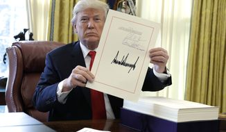 "President Donald Trump displays the $1.5 trillion tax overhaul package he had just signed, Friday, Dec. 22, 2017, in the Oval Office of the White House in Washington. Trump touted the size of the tax cut, declaring to reporters in the Oval Office before he signed it Friday that ""the numbers will speak."" (AP Photo/Evan Vucci)"