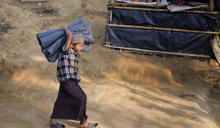 A Rohingya Muslim child carrying a blanket at Kutupalong refugee camp in Ukhiya, Bangladesh, Thursday, Dec. 21, 2017.  Many thousands of Rohingya people have crossed over from Myanmar into Bangladesh.  (AP Photo/A.M. Ahad)