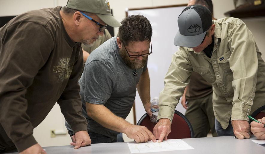 In this Friday, Dec. 15, 2017 photo, John Harris, from left, of Henderson, Dave Raynor, of Boulder City, and Darrel Leavitt, of Las Vegas, attend an orientation at the Clark County Shooting Complex for hunters randomly picked for the annual bighorn sheep hunt inside the Nevada Test and Training Range, in Las Vegas. (Erik Verduzco/Las Vegas Review-Journal via AP)