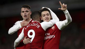 Arsenal's Mesut Ozil, right, celebrates scoring his side's third goal of the game during their English Premier League soccer match between Arsenal and Liverpool at the Emirates stadium London, Friday, Dec. 22, 2017. (John Walton/PA via AP)