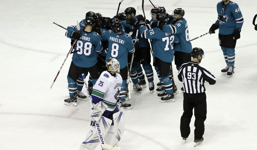 Vancouver Canucks goalie Jacob Markstrom (25) skates off the ice as the San Jose Sharks celebrate an overtime goal by Kevin Labanc during an NHL hockey game Thursday, Dec. 21, 2017, in San Jose, Calif. San Jose won 5-4. (AP Photo/Marcio Jose Sanchez)