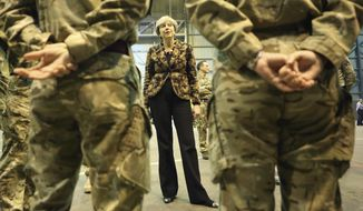 British Prime Minister Theresa May speaks with troops serving at RAF Akrotiri, one of two military bases Britain maintains on the east Mediterranean island of Cyprus on Thursday, Dec. 21, 2017. May stopped off at RAF Akrotiri to deliver good wishes to  service personnel for the upcoming holidays on her way back to the UK after a visit to Poland. (AP Photo/Petros Karadjias, Pool)