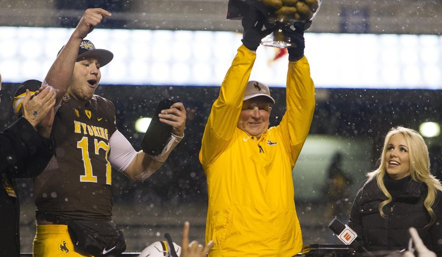 Wyoming quarterback Josh Allen (17) celebrates with coach Craig Bohl after receiving the Famous Idaho Potato Bowl trophy after Wyoming defeated Central Michigan 37-14 in the NCAA college football game Friday, Dec. 22, 2017, in Boise, Idaho. (Darin Oswald/Idaho Statesman via AP)