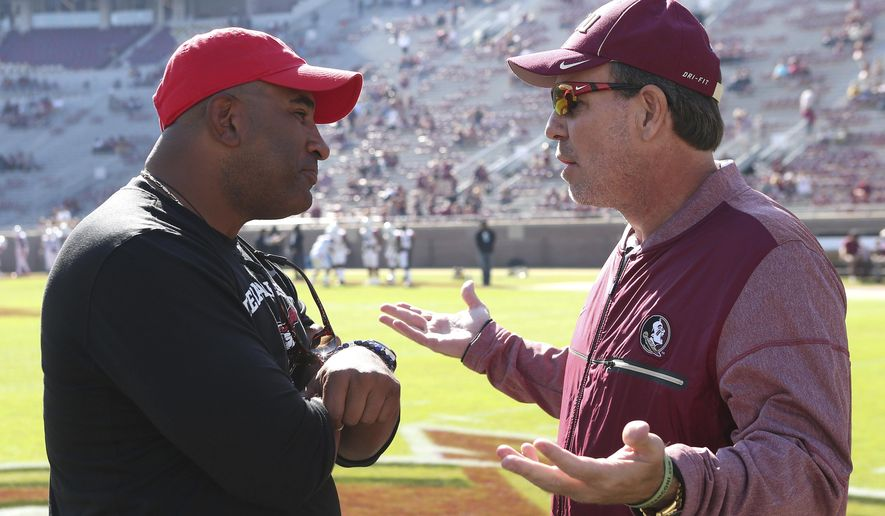 FILE - In this Nov. 18, 2017, file photo, Florida State's head coach Jimbo Fisher, right, meets Delaware State's head coach Kenny Carter at midfield before the start of an NCAA college football game in Tallahassee Fla. The latest issue in a mostly forgettable season for Florida State is a possible administrative error, apparently discovered by a Reddit user, that calls into question the Seminoles' bowl eligibility. The Independence Bowl between Florida State and Southern Miss will go on, regardless, and Seminoles fans can only hope that they can finally put 2017 to rest.(AP Photo/Steve Cannon, File)