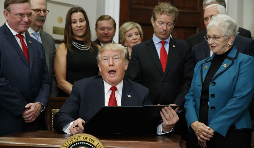 In this Oct. 12, 2017 file photo, President Donald Trump speaks before signing an executive order on health care in the Roosevelt Room of the White House in Washington. An Associated Press analysis finds that Americans in states President Donald Trump carried account for more than 4 in 5 of those signed up for coverage under the health care law he still wants to take down.  (AP Photo/Evan Vucci)