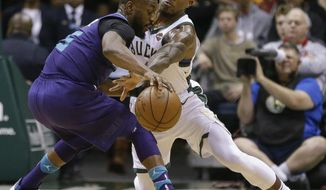 Milwaukee Bucks' Eric Bledsoe makes a steal attempt on Charlotte Hornets' Nicolas Batum, left, during the second half of an NBA basketball game Friday, Dec. 22, 2017, in Milwaukee. (AP Photo/Tom Lynn)