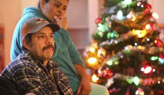 Martin Chairez-Castrejon talks about his ongoing struggles with Immigration and Customs Enforcement at home in Salt Lake City on Friday, Dec. 15, 2017. His wife Lorena is behind him. (Kristin Murphy/Deseret News via AP)