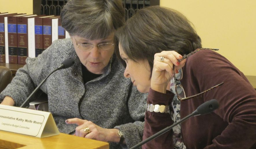In this Wednesday, Dec. 20, 2017 photo, Kansas state Sen. Laura Kelly, left, D-Topeka, and state Rep. Kathy Wolfe Moore, right, D-Kansas City, confer during a committee briefing on a proposal to build a new state prison, at the Statehouse in Topeka, Kan. The briefing bolstered support for the project among top Republican lawmakers who will help decide whether the project moves forward. (AP Photo/John Hanna)