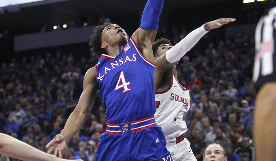Kansas guard Devonte' Graham (4) drives to the basket against Stanford defender Daejon Davis during the first half of an NCAA college basketball game in Sacramento, Calif., Thursday, Dec. 21, 2017. (AP Photo/Steve Yeater)