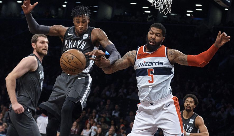 Washington Wizards' Markieff Morris, right, competes for the ball with Brooklyn Nets' Rondae Hollis-Jefferson during the first half of an NBA basketball game Friday, Dec. 22, 2017, in New York. (AP Photo/Andres Kudacki)
