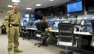 FILE - In this Nov. 3, 2015, file photo, Max Raterman, left, who directs the U.S. Customs and Border Protection Air and Marine Operations at Grand Forks Air Force Base, N.D, monitors work in the operations center. Contract employee Jeff Deem, right, is following an unmanned flight that originated at the center. The CBP is offering part-time jobs to underclassmen at the University of North Dakota with hopes they will want to help protect the country when they graduate. (AP Photo/Dave Kolpack File)