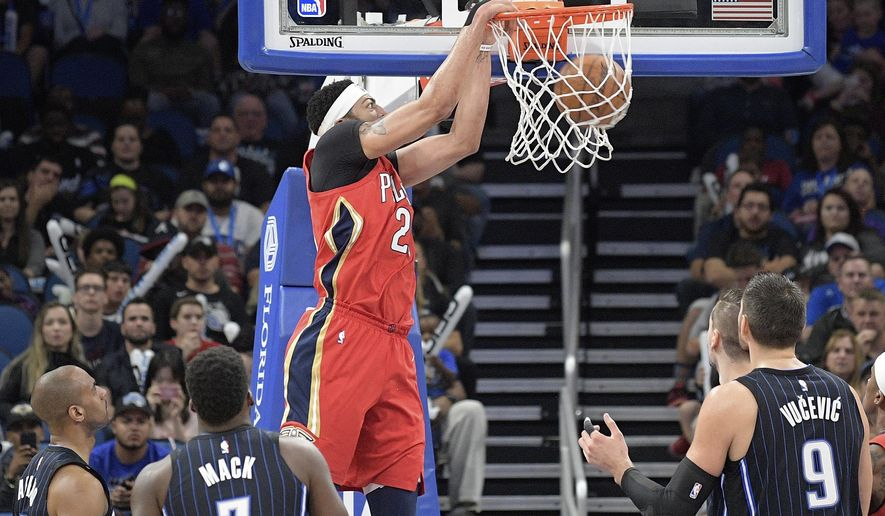 New Orleans Pelicans forward Anthony Davis, center, dunks between Orlando Magic guard Arron Afflalo (4), guard Shelvin Mack (7) and center Nikola Vucevic (9) during the first half of an NBA basketball game Friday, Dec. 22, 2017, in Orlando, Fla. (AP Photo/Phelan M. Ebenhack)