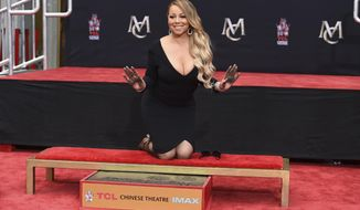 """FILE - In this Wednesday, Nov. 1, 2017, file photo, Mariah Carey poses for photographers during her hand and footprint ceremony at the TCL Chinese Theatre in Los Angeles. Carey is returning to """"Dick Clark's New Year's Rockin' Eve with Ryan Seacrest"""" after last year's debacle. They released a joint statement Friday, Dec. 22,2017,  acknowledging problems with last year's show and saying they are thrilled to have """"an incredible night of music and celebration"""" planned.(Photo by Jordan Strauss/Invision/AP, File)"""