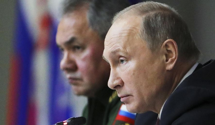 Russian President Vladimir Putin, foreground, Russian Defence Minister Sergei Shoigu, attend a meeting while visiting the Military Academy of Strategic Rocket Troops of the Peter the Great in Balashikha, outside Moscow, Russia, Friday, Dec. 22, 2017. Russian President Vladimir Putin is accusing the U.S. of violating a landmark Cold War-era arms nuclear pact. (Mikhail Klimentyev, Sputnik, Kremlin Pool Photo via AP)