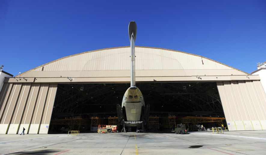 FILE - In this Oct. 30, 2014 file photo, the tail of a C5 Galaxy aircraft sticks out the door of Building 125 at Robins Air Force Base in Warner Robins, Ga.  Radio interference from a farm's massive metal crop-watering structure is causing havoc for air traffic in the sky over Georgia, federal authorities said in a lawsuit filed this week. The irrigation structure is on a south Georgia farm where the Federal Aviation Administration has a radio transmitter to relay signals that keep aircraft on course, according to the federal lawsuit.  (Woody Marshall/The Macon Telegraph via AP)