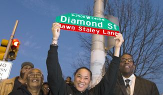 In this Wednesday, Dec. 20, 2017 photo, Dawn Staley holds a sign as she poses with Cheryl Hardy, director of the Gathers Rec Center, left and President of the City Council Darrell Clarke in Philadelphia. A portion of W. Diamond St, from 23rd St to 25th St., has been renamed Dawn Staley Lane. (Charles Fox/The Philadelphia Inquirer via AP)
