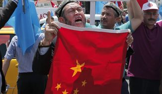 FILE - In this file photo taken Sunday, July 5, 2015, Uighurs living in Turkey and Turkish supporters, chant slogans as they hold a Chinese flag before burning it during a protest near China's consulate in Istanbul, against what they call oppression by Chinese government to Muslim Uighurs in far-western Xinjiang region. Since 2013, thousands of Uighurs, a Turkic-speaking Muslim minority from western China, have traveled to Syria to train and fight alongside al-Qaida, playing key roles in several battles.  (AP Photo/Lefteris Pitarakis, File)