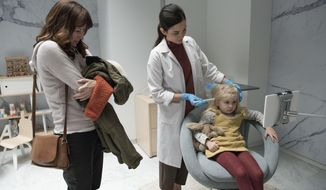 """This image released by Netflix shows Rosemarie Dewitt, left, and Aniya Hodge, seated right, in an episode of """"Black Mirror,"""" directed by Jodie Foster. Season four of """"Black Mirror,"""" will be available for streaming on Netflix starting Dec. 29. (Christos Kalohoridis/Netflix via AP)"""