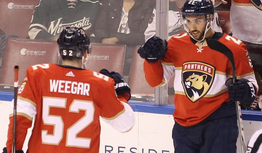 Florida Panthers' Vincent Trocheck, right, celebrates with teammate MacKenzie Weegar (52) after scoring a goal against the Minnesota Wild during the first period of an NHL hockey game, Friday, Dec. 22, 2017, in Sunrise, Fla. (AP Photo/Luis M. Alvarez)