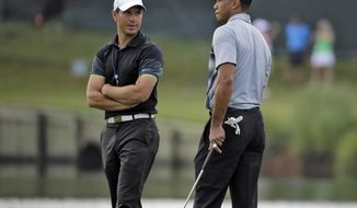 FILE - In this May 6, 2015, file photo, Tiger Woods, right, talks with swing coach Chris Como on the 17th green during a practice round for The Players Championship golf tournament at Sawgrass in Ponte Vedra Beach, Fla. Woods is embarking on his latest comeback without a swing coach, saying he has worked hard to relearn his body and the golf swing. Como has helped him the last three years. (AP Photo/Chris O'Meara, File)