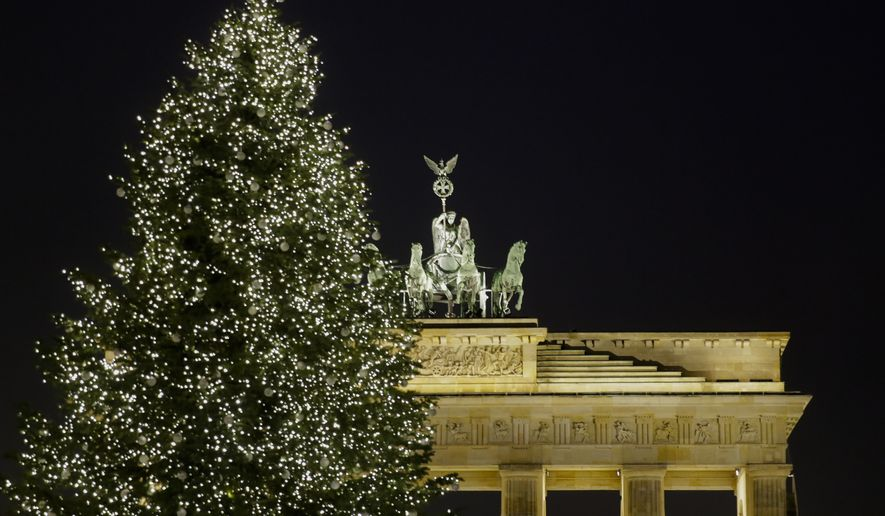 A Christmas tree is illuminated in front of Germany's landmark Brandenburg Gate a day before Christmas Eve in Berlin, Saturday, Dec. 23, 2017. (AP Photo/Markus Schreiber) **FILE**
