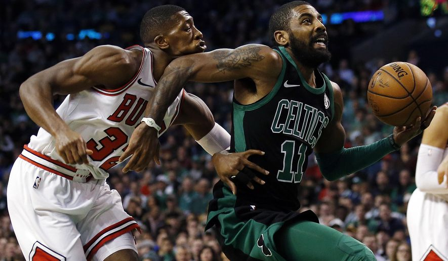 Boston Celtics' Kyrie Irving elbows Chicago Bulls' Kris Dunn on the face as he goes past Dunn to the basket during the first quarter of an NBA basketball game in Boston on Saturday, Dec. 23, 2017. (AP Photo/Winslow Townson)