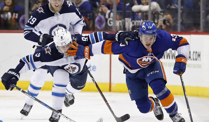 New York Islanders center Mathew Barzal (13) controls the puck against Winnipeg Jets center Andrew Copp (9) in the second period of an NHL hockey game, Saturday, Dec. 23, 2017, in New York. (AP Photo/Adam Hunger)