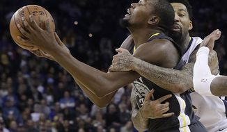Golden State Warriors forward Kevin Durant, left, is fouled by Denver Nuggets forward Wilson Chandler during the second half of an NBA basketball game in Oakland, Calif., Saturday, Dec. 23, 2017. The Nuggets won 96-81. (AP Photo/Jeff Chiu)