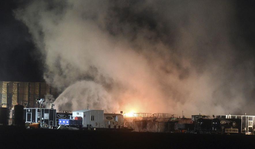 Firefighters douse some of the flames from a fire at an active oil and gas site Friday, Dec. 22, 2017, near Windsor, Colo. An investigation is underway after a worker was injured in a fire at the oil site in northern Colorado. The Weld County Sheriff's Office says the fire was reported on Friday night, and the worker was taken to a nearby hospital with undisclosed injuries. (Joshua Polson/The Greeley Tribune via AP)