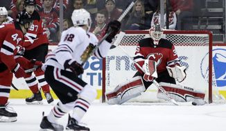 New Jersey Devils goalie Cory Schneider right, deflects a shot by the Chicago Blackhawks during the second period of an NHL hockey game, Saturday, Dec. 23, 2017, in Newark, N.J. (AP Photo/Julio Cortez)