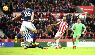 Stoke City's Eric Maxim Choupo-Moting, center, scores his side's second goal of the game during the English Premier League soccer match at the Bet365 Stadium, in Stoke, England, Saturday, Dec. 23, 2017. (Dave Thompson/PA via AP)
