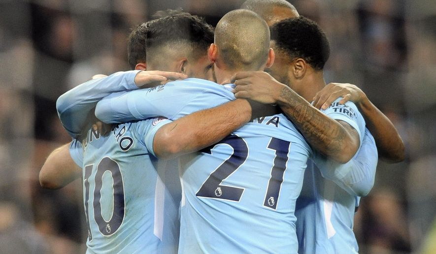Manchester City's Sergio Aguero, left, celebrates with teammates after scoring his second goal, his side's third, during the English Premier League soccer match between Manchester City and Bournemouth at Etihad stadium, in Manchester, England, Saturday, Dec. 23, 2017. (AP Photo/Rui Vieira)