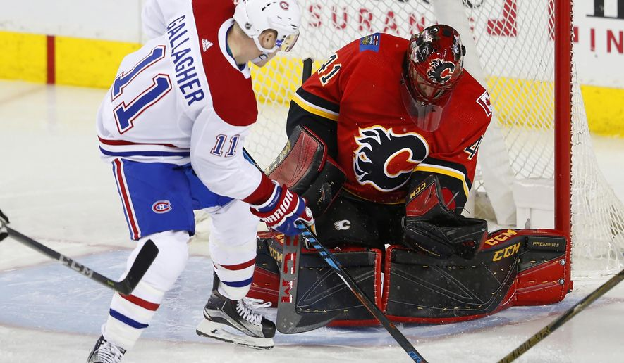 Calgary Flames goalie Mike Smith makes a save on Montreal Canadiens' Brendan Gallagher during the third period of an NHL hockey game Friday, Dec. 22, 2017, in Calgary, Alberta. (Todd Korol/The Canadian Press via AP)