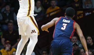 Minnesota's Nate Mason, left, shoots as Florida Atlantic's Anthony Adger watches in the first half of an NCAA college basketball game Saturday, Dec. 23, 2017, in Minneapolis. (AP Photo/Jim Mone)