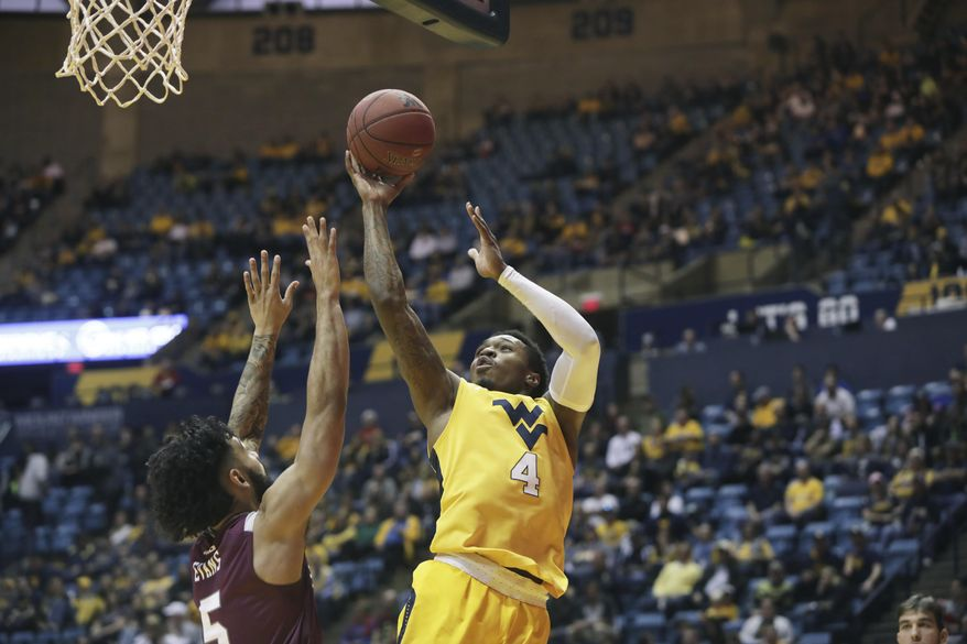 West Virginia guard Daxter Miles Jr. (4) shoots while being defended by Fordham guard Tre Evans (5) during the first half of an NCAA college basketball game Saturday, Dec. 23, 2017, in Morgantown, W.Va. (AP Photo/Raymond Thompson)