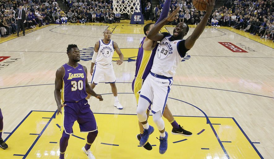Golden State Warriors forward Draymond Green (23) drives to the basket past Los Angeles Lakers forward Kyle Kuzma as Lakers forward Julius Randle (30) watches during the first half of an NBA basketball game Friday, Dec. 22, 2017, in Oakland, Calif. (AP Photo/Marcio Jose Sanchez)