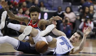 Washington Wizards forward Kelly Oubre Jr., left, competes for a loose ball with Orlando Magic guard Mario Hezonja, from Croatia, during the first half of an NBA basketball game Saturday, Dec. 23, 2017, in Washington. (AP Photo/Alex Brandon)