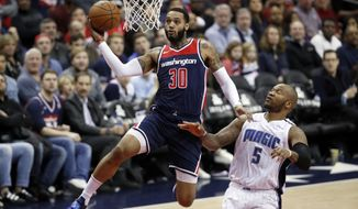 Washington Wizards forward Mike Scott (30) drives past Orlando Magic forward Marreese Speights (5) for a shot during the second half of an NBA basketball game Saturday, Dec. 23, 2017, in Washington. The Wizards won 130-103. (AP Photo/Alex Brandon)