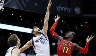 Atlanta Hawks' Dennis Schroder, right, of Germany, shoots over Dallas Mavericks' Maximilian Kleber, also of Germany, in the first quarter of an NBA basketball game in Atlanta, Saturday, Dec. 23, 2017. (AP Photo/David Goldman)